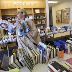 Children's assistant librarian Elisa Hallett carries books to the curbside delivery area at the Springville Library in Springville on Wednesday, April 8, 2020.