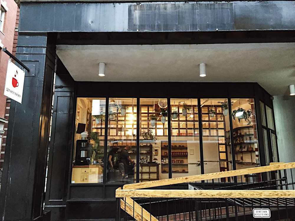 Exterior shot of a cafe, with coffee apparatus, cafe employees, and white vases holding green plants visible through floor-to-ceiling windows.