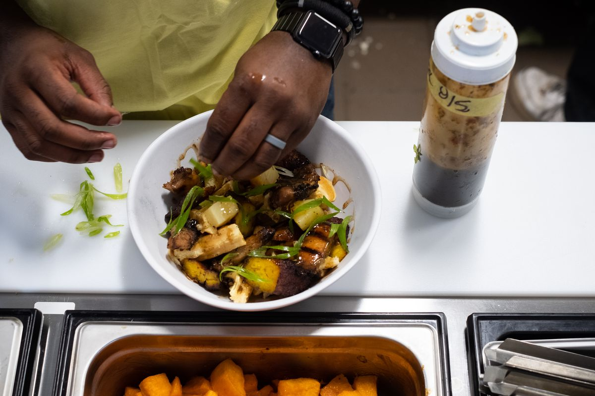 The chef's hand hovers over a bowl full of plantains, waffle pieces, and jerk chicken