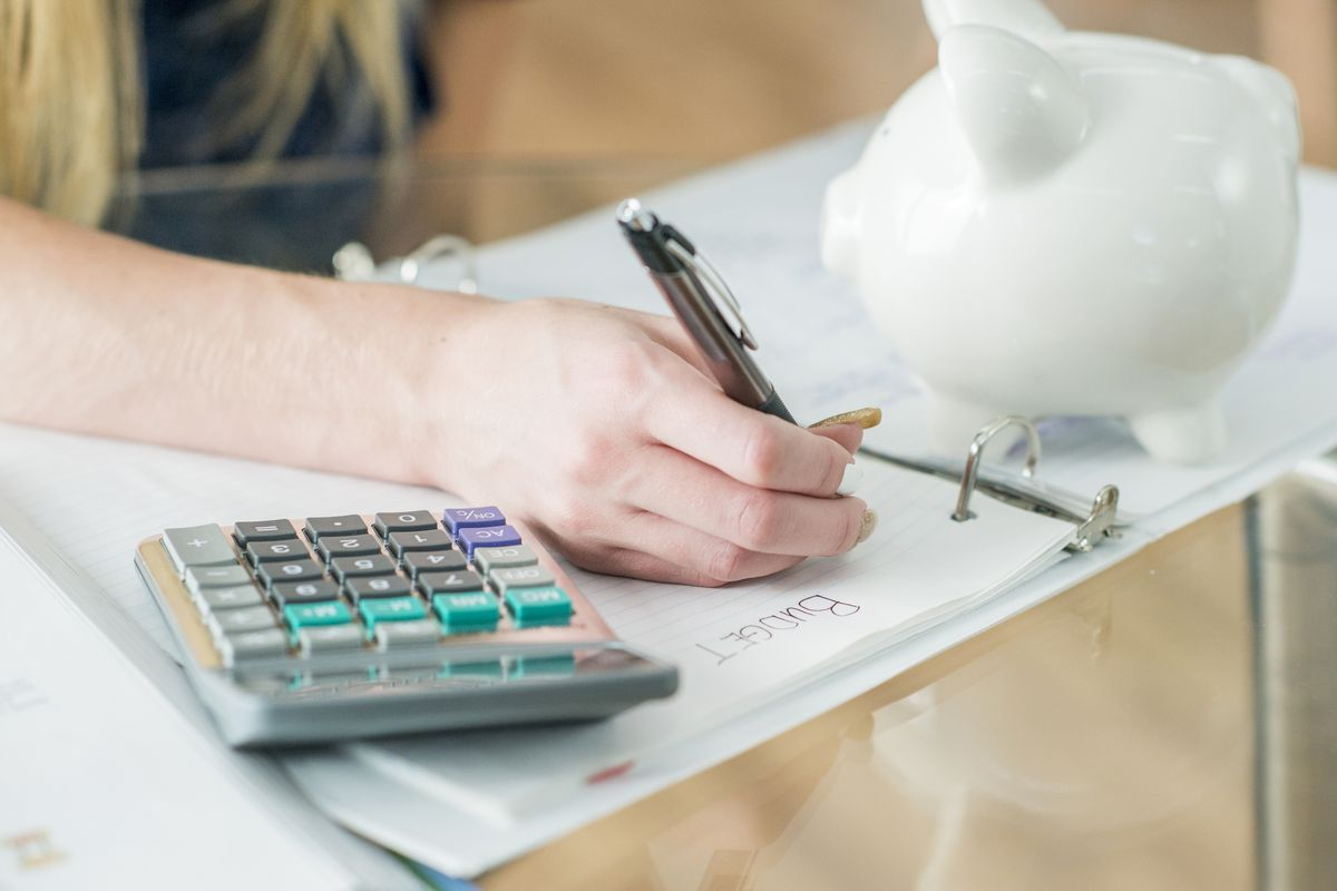 A girl writes in a notebook, with a calculator and white piggy bank sitting on the desk.