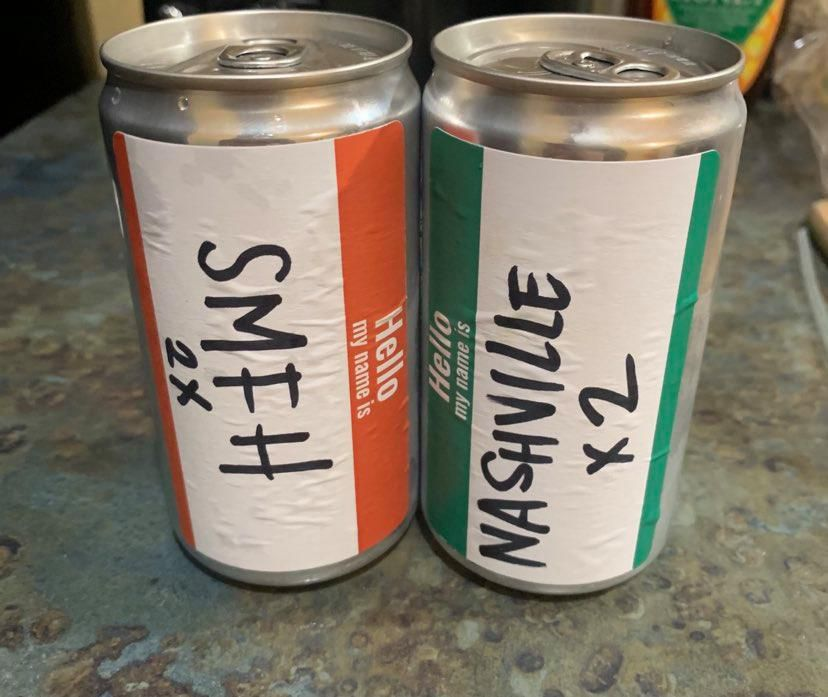 Two cans, one labeled SMFH x2 and the other Nashville x2, rest on a counter