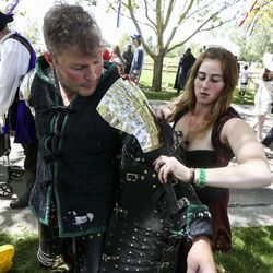 Arianna Allred helps fiancé Glenn Canchola into his armor before the Armored Combat League fights during the Utah Renaissance Faireat Thanksgiving Point's Electric Park in Lehi on Friday, Aug. 23, 2019.