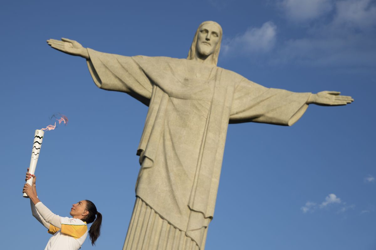 Brazil's former volleyball player Isabel carries the Olympic torch in front of the Christ the Redeemer statue on its way for the opening ceremony of Rio's 2016 Summer Olympics in Rio de Janeiro, Brazil, Friday, Aug. 5, 2016. (AP Photo/Felipe Dana)