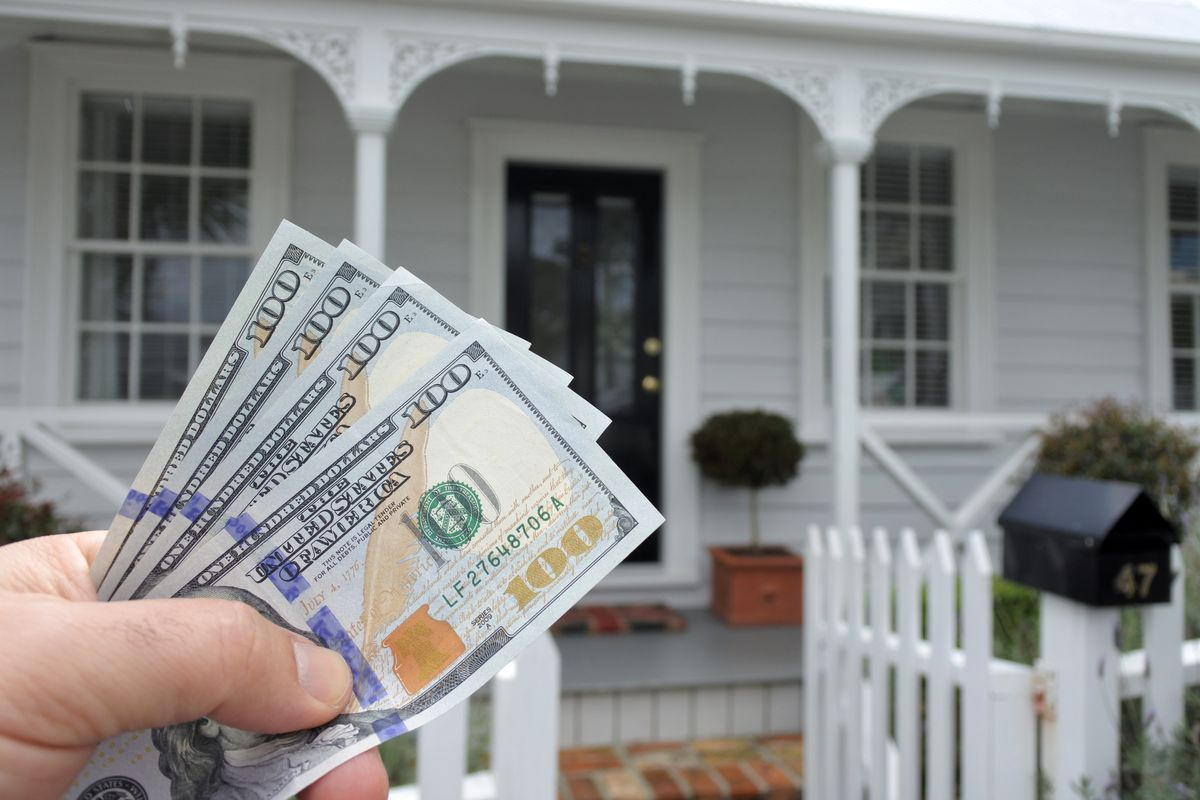 A mans hand holds US dollar bills against a front of North American house.