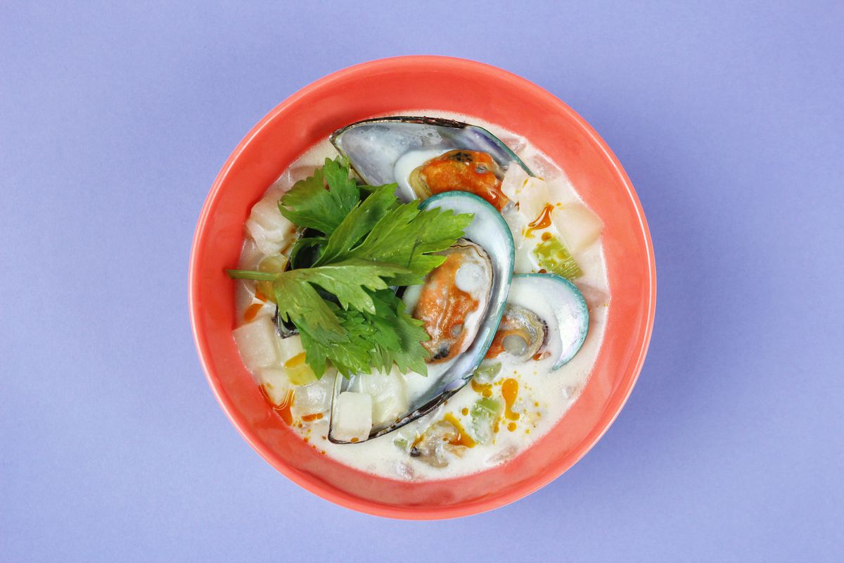 A red bowl filled with white soup, blue mussels, and green herbs sits on a light blue background.