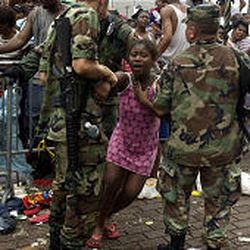 A woman is carried Thursday from a holding area after fainting at the Superdome during relief efforts of Hurricane Katrina in New Orleans. The crowds at the New Orleans arena have suffered in hot, smelly conditions with few supplies and no air conditioning.
