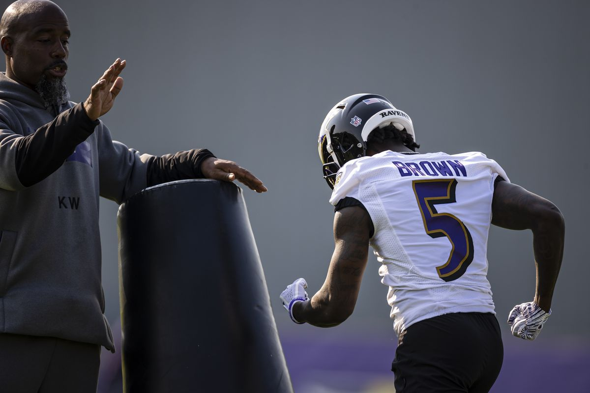 Pass game specialist Keith Williams speaks as Marquise Brown #5 of the Baltimore Ravens pushes a tackling dummy during training camp at Under Armour Performance Center Baltimore Ravens on July 28, 2021 in Owings Mills, Maryland.