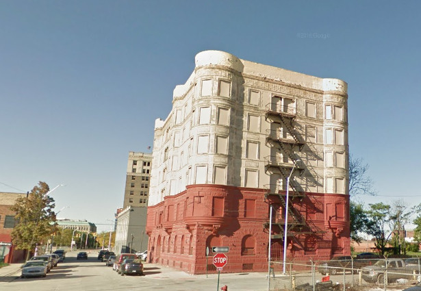 The exterior of the Alhambra apartments in Detroit. The facade is white and red with boarded up windows.