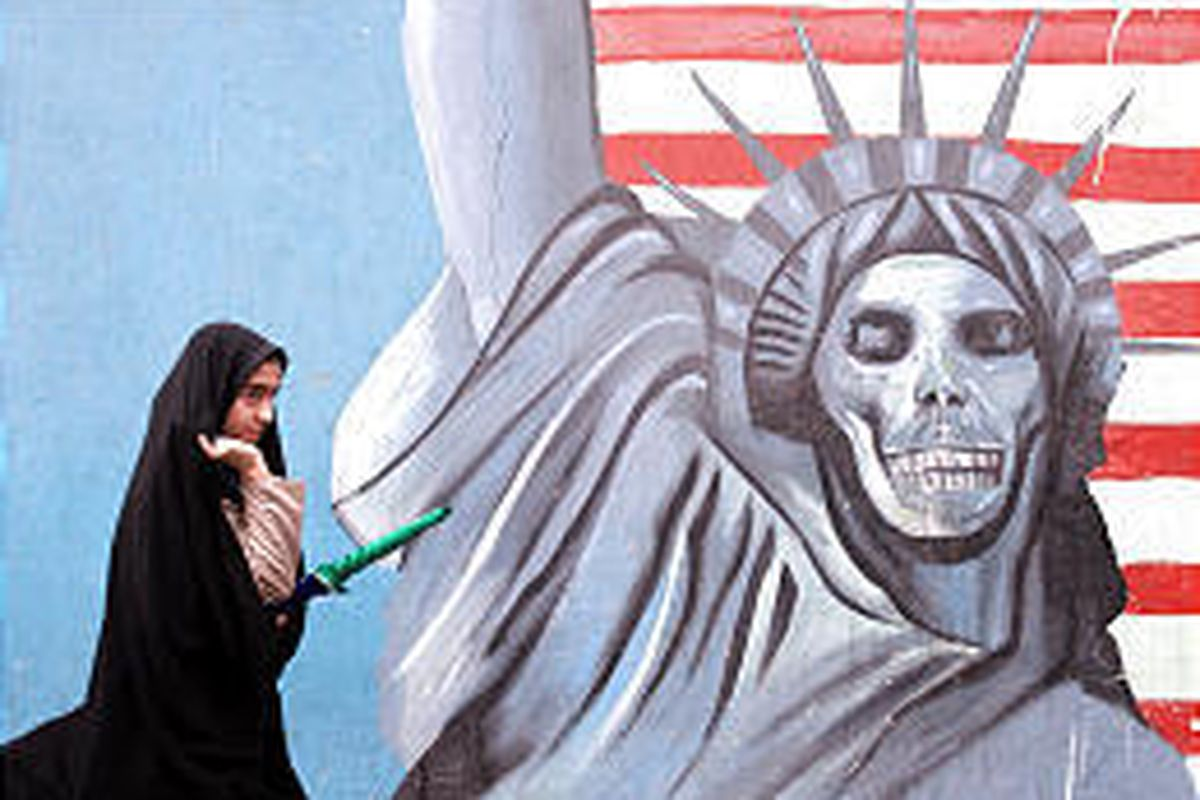 An Iranian woman walks past a satirized drawing of the Statue of Liberty painted on the wall of the former U.S. Embassy in Tehran, Iran.