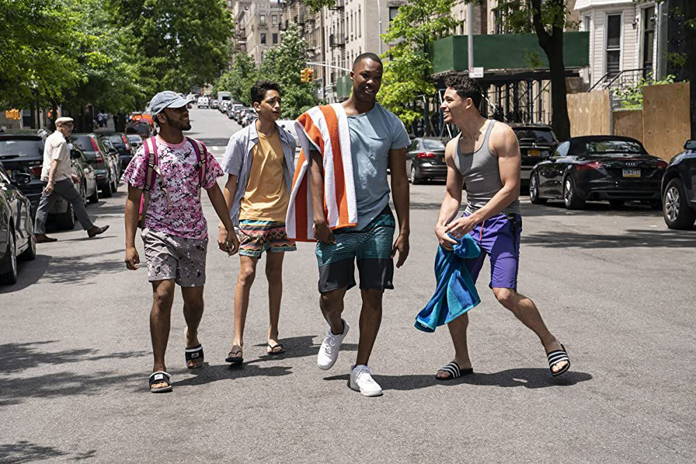 A group of four young men dressed in swimsuits head down a city block for a pool.