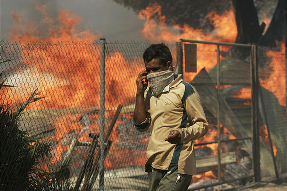 A man walks by a burning house in Dioni, 25 miles east of Athens, Monday. Subsiding winds helped firefighters.