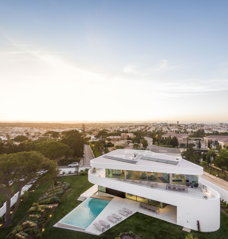Aerial shot of triangular white house with terraces and a ground-level pool.