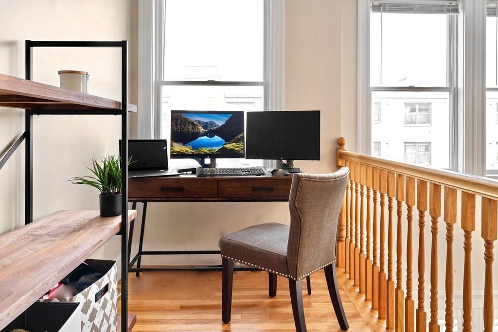 A desk and a chair next to some shelves on a stairs landing.