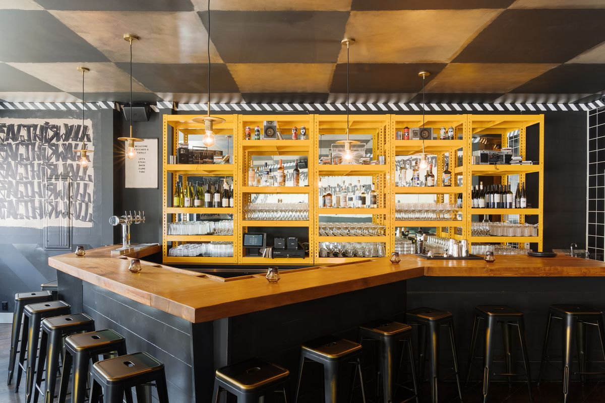 A head-on shot of an angular bar counter, with bright yellow trim, lots of black bar stools, and some natural light