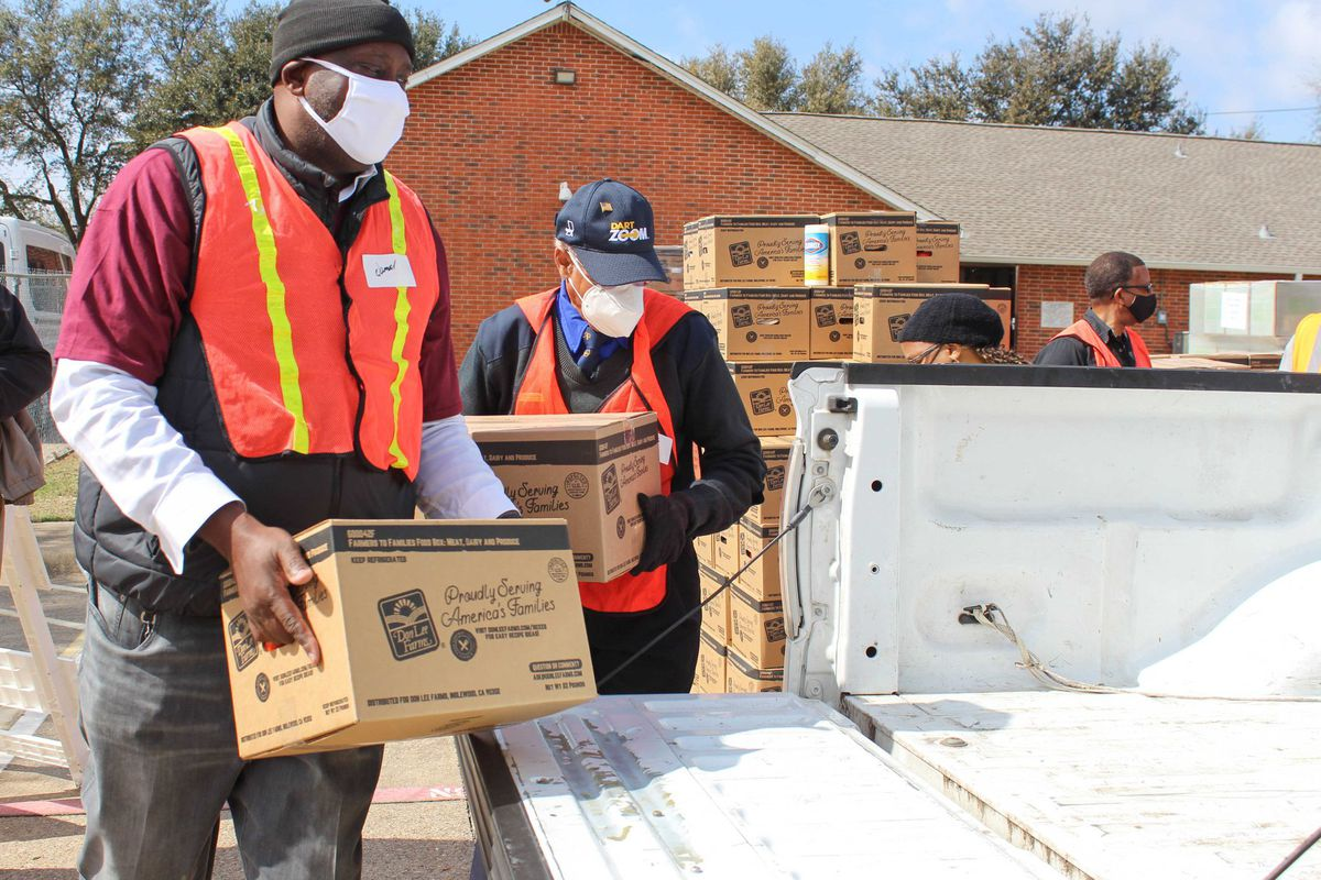 Two masked men in orange safety vests load boxes of food into the bed of a white pickup truck at a food bank.