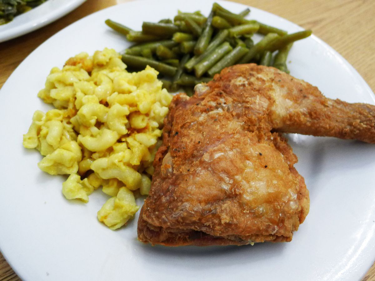 A white plate with fried chicken, mac and cheese, and green beans