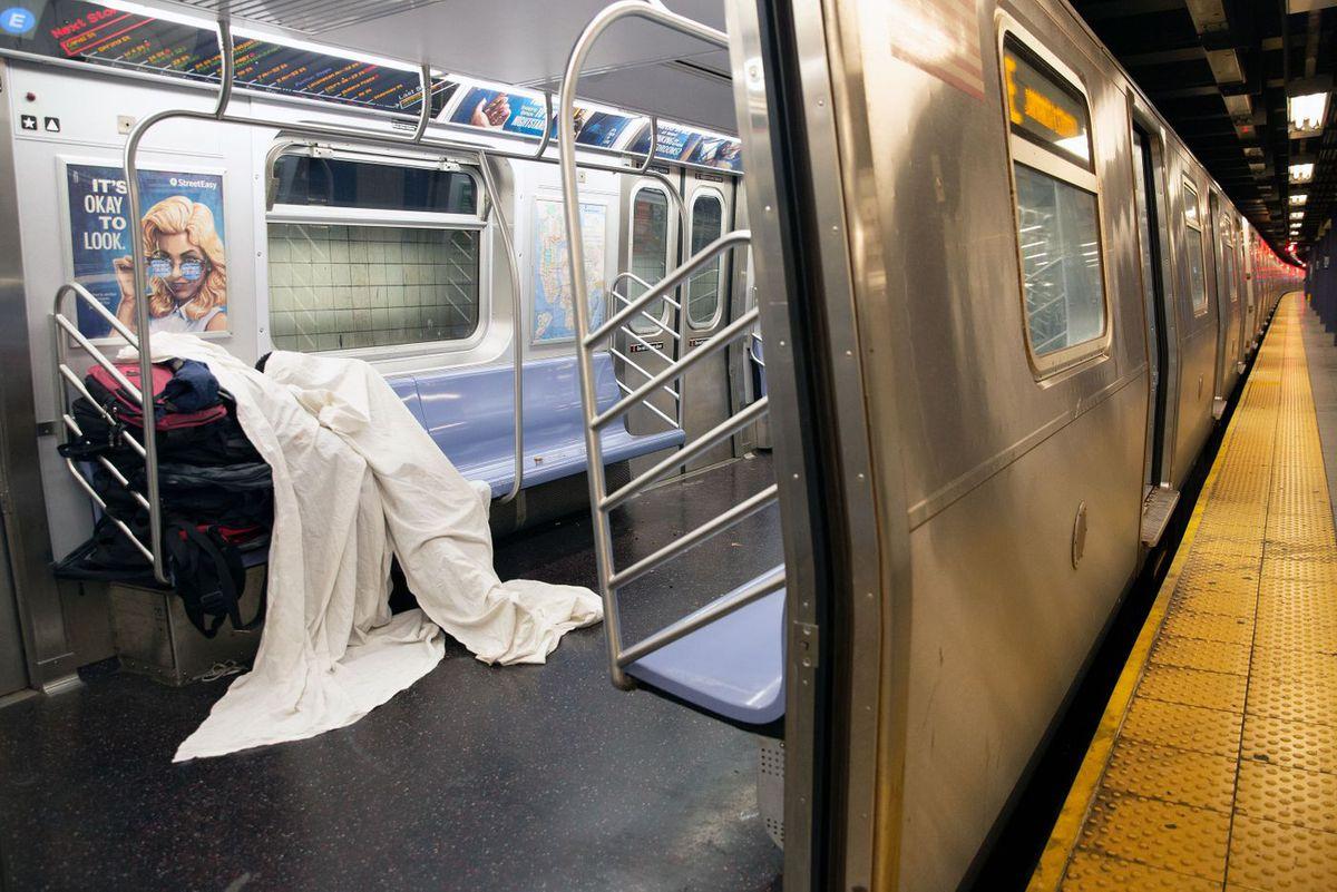 A homeless person sleeps on an E train.