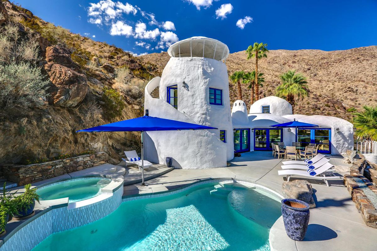 An exterior view of a white cave-like house with blue accents designed by William Nicholson. There's a pool in front of the home.