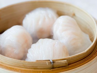 A bamboo steamer teaming with white-and-pink dumplings.