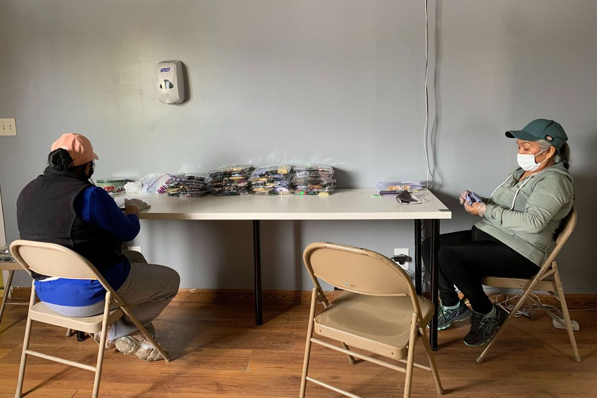 Sofia Reyes, left, and Benita Sanchez prepare and package masks on the second floor of La Colmena, a community job center in Port Richmond where the women work on Mondays and Wednesdays.