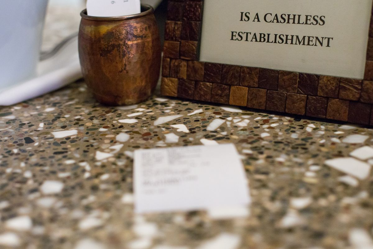 A check for food sits on a marble table at a restaurant with a sign in the back that reads cashless establishment