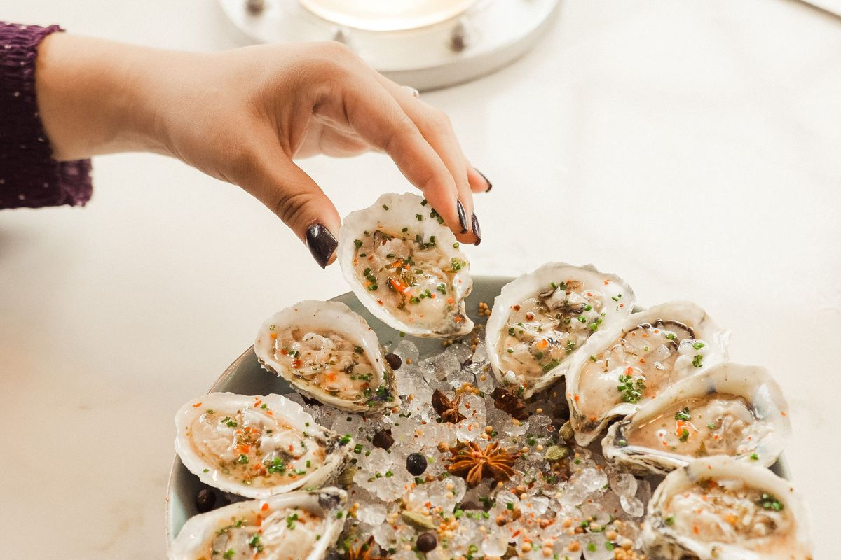 a hand grabbing a raw oyster from a plate of a dozen ousters on the half shell