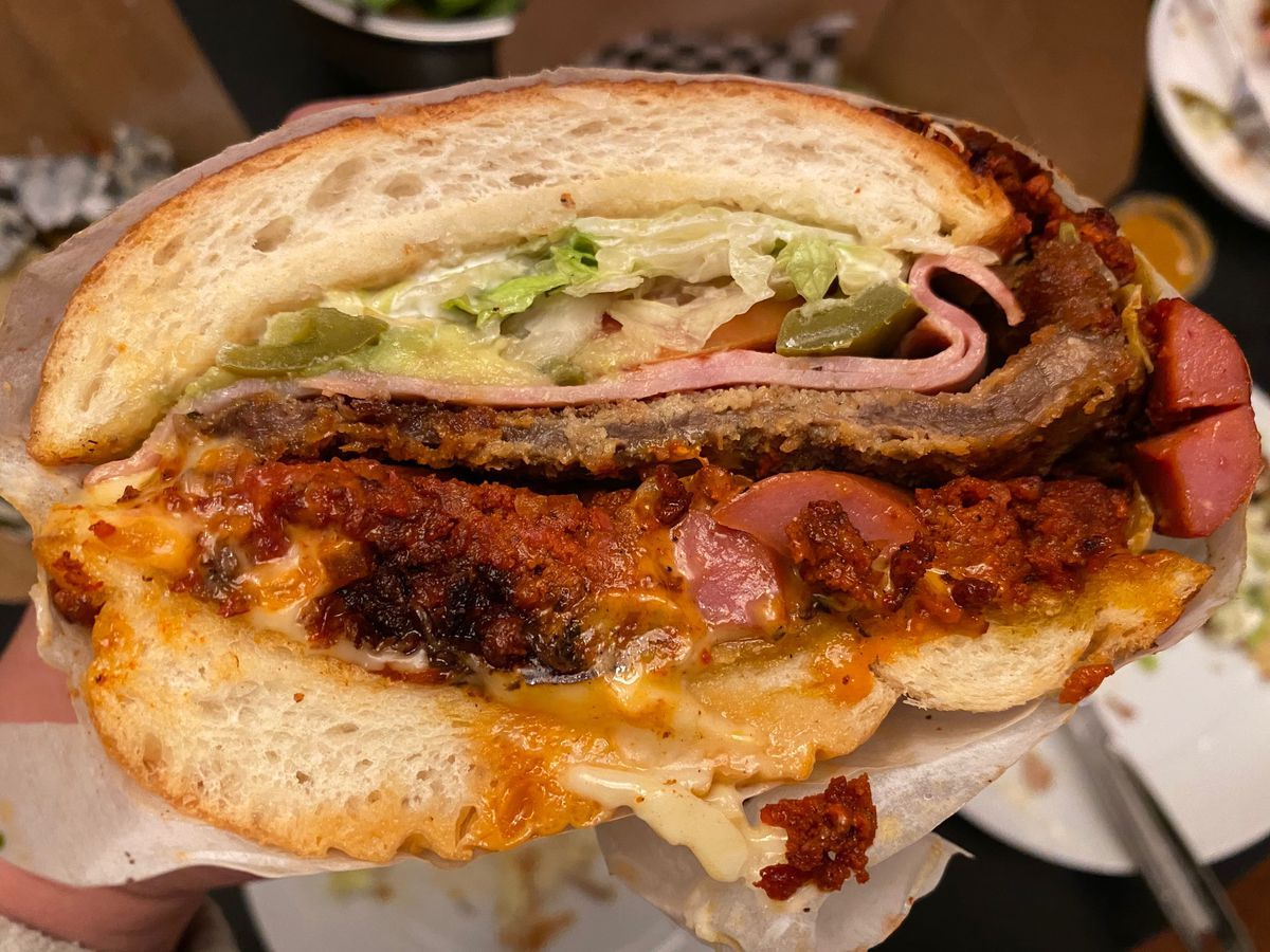 Cross section of a torta Cubana, which is stuffed with meats: chorizo, sausage, fried steak cutlet, and ham