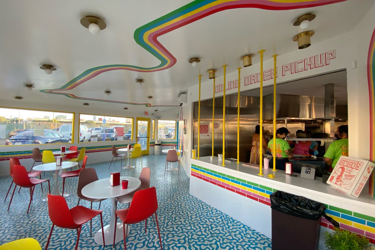 Interior of Gogo's Tacos in Los Angeles, with lines and white trim and red chairs.