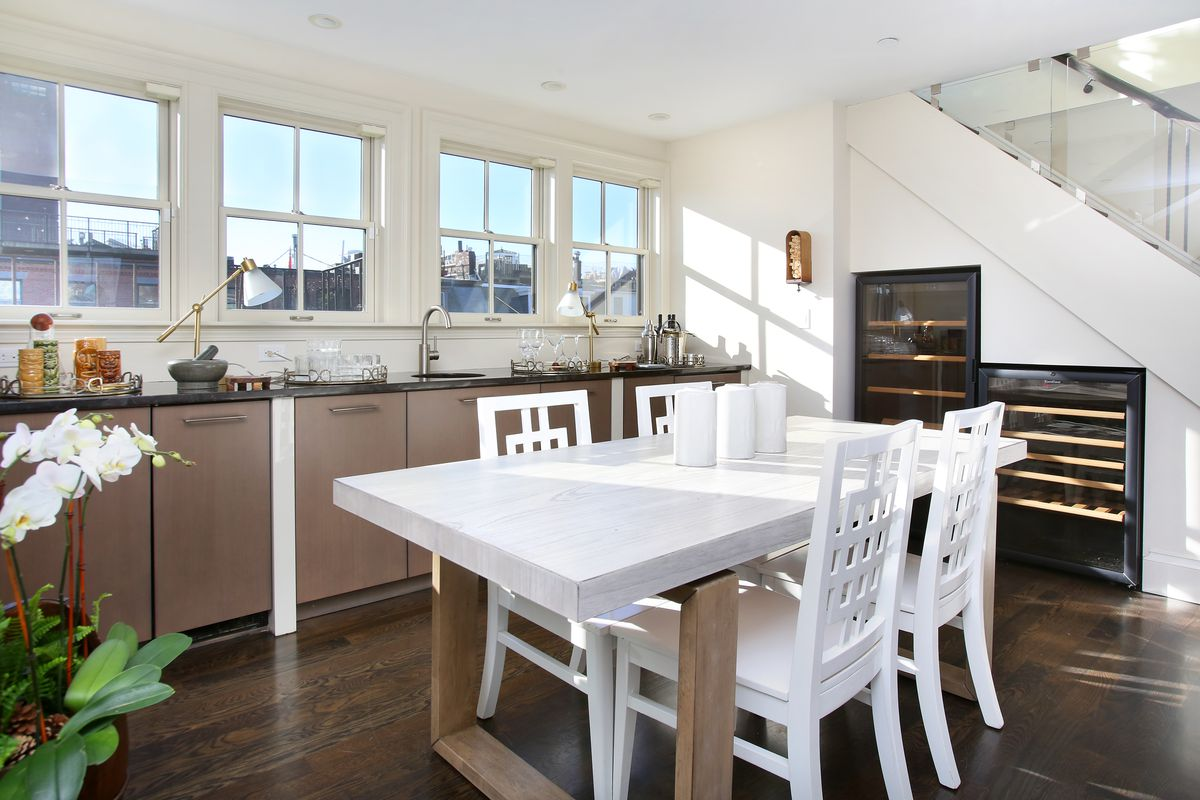 A modern open kitchen with windows over the counter and a table with chairs.
