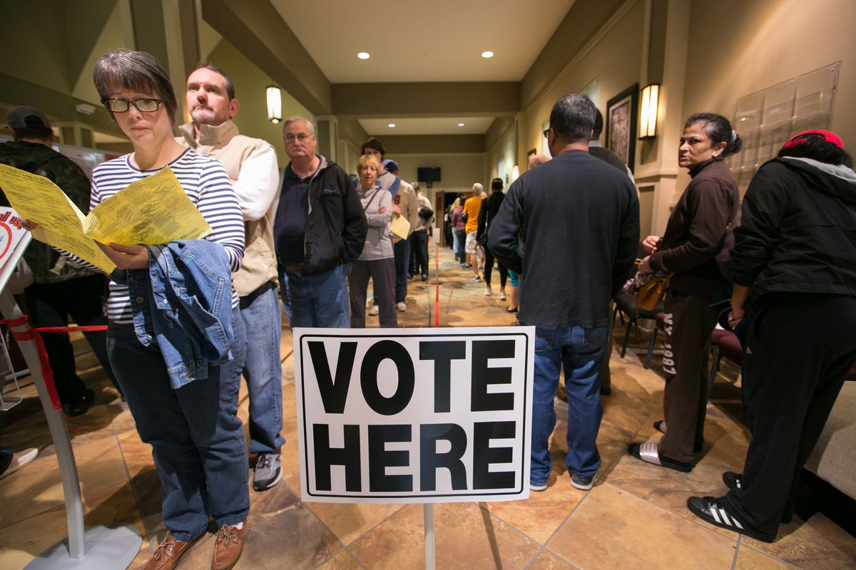 """Voters line up to cast their ballots at a polling station beside a sign that reads, """"Vote here."""""""