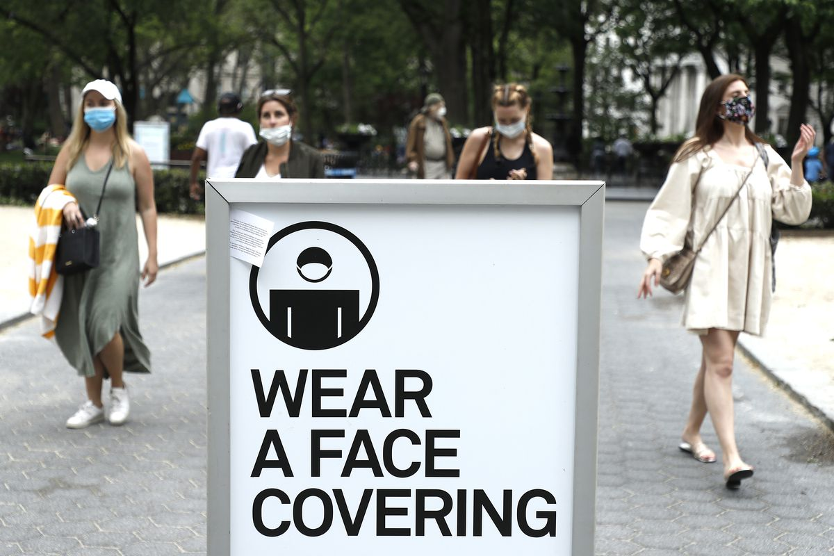 """Women wear masks in a public park while walking around a cautionary sign that reads, """"Wear a face covering."""""""