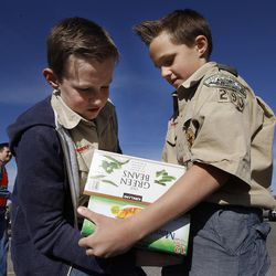 From left, Boy Scouts Evan Hofheins and Ashton Hofheins participate in a food drive assembly line in South Jordan on Saturday, March 21, 2015.