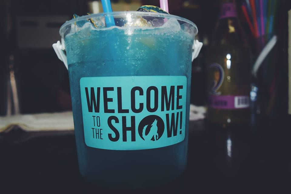 """A large plastic bucket is filled with a bright blue cocktail. A label that says """"Welcome to the show!"""" is plastered on the bucket."""