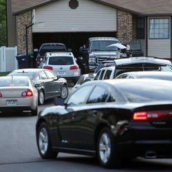 After serving a search warrant Monday, June 2, 2014, local and federal authorities leave the home of former Attorney General John Swallow in Sandy.