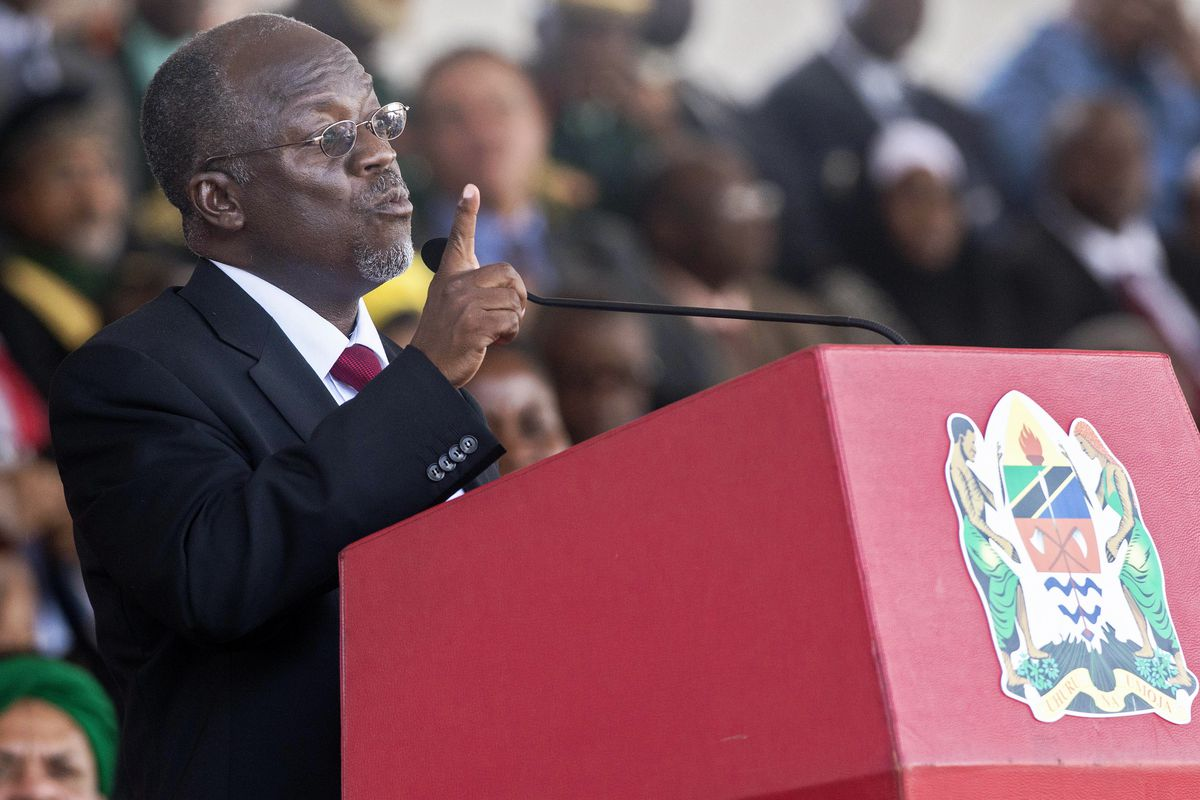 John Magufuli stands at a red lectern with a crowd in the background.