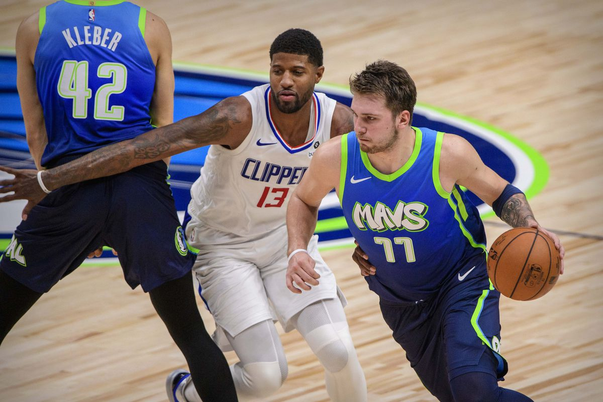 LA Clippers forward Paul George and Dallas Mavericks forward Luka Doncic in action during the game between the Mavericks and the Clippers at the American Airlines Center.