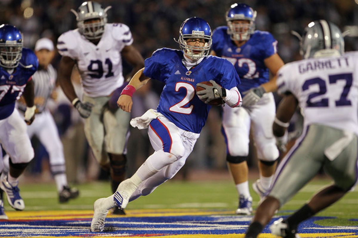 Quarterback Jordan Webb #2 of the Kansas Jayhawks scrambles as David Garrett #27 of the Kansas State Wildcats defends during the game at Memorial Stadium in Lawrence Kansas.  (Photo by Jamie Squire/Getty Images)