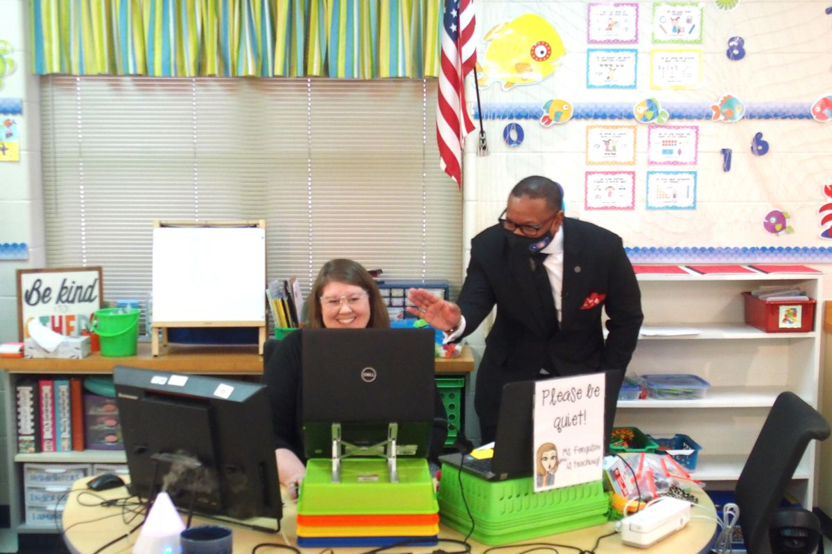 Superintendent Joris Ray bends down to wave at kindergarten students on a laptop screen who are in an online class while their teacher smiles at her desk.