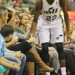 Utah's Justin Holiday runs into a group of ladies on the front row as the Utah Jazz and the Golden State Warriors play Tuesday, Oct. 8, 2013 in preseason action at Energy Solutions arena in Salt Lake City.