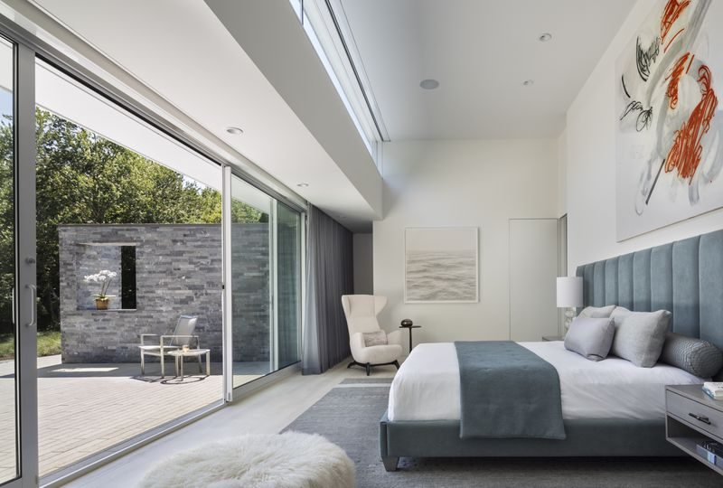 High-ceilinged bedroom with sliding glass doors to a terrace.