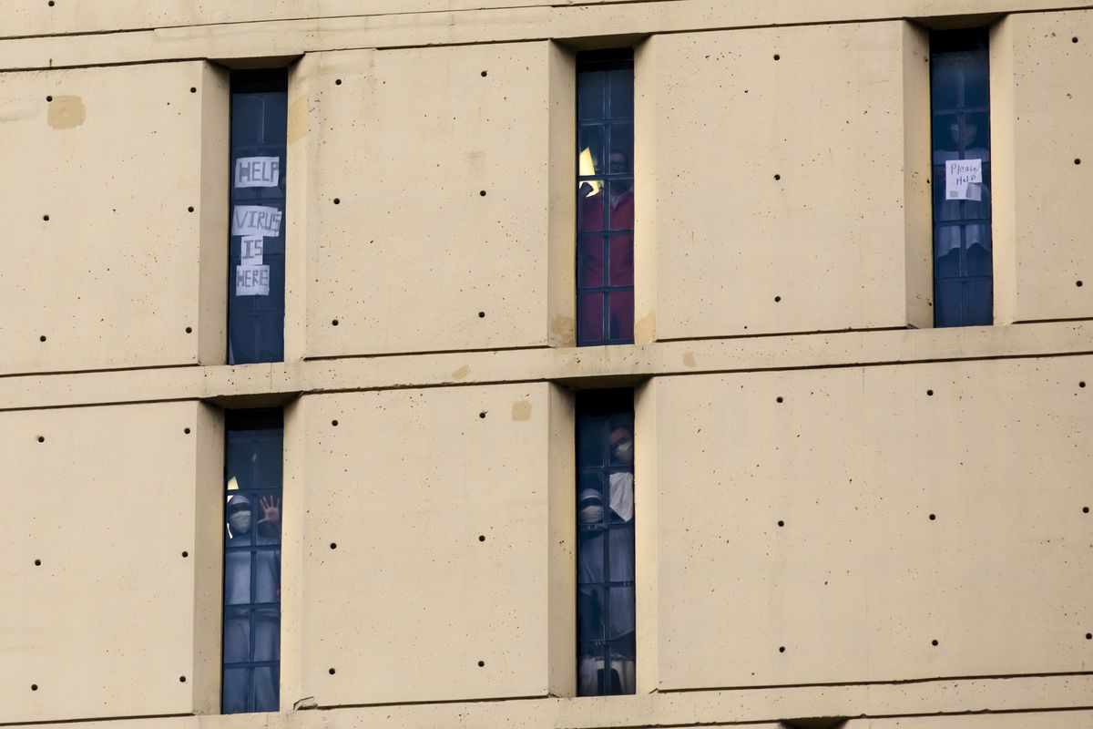 Inmates at the Metropolitan Correctional Center hold up signs asking for help during the coronavirus pandemic, Monday afternoon, April 20, 2020.