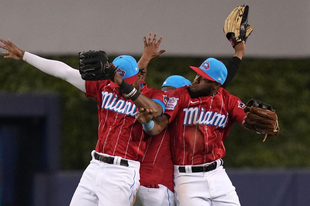 Miami Marlins center fielder Lewis Brinson (25), center fielder Magneuris Sierra (34) and right fielder Bryan De La Cruz (77) celebrate after defeating the Chicago Cubs at loanDepot park