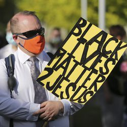 Michael Stanger holds a sign during a fast, march and prayer vigil for racial injustice at the University of Utah Institute of Religion in Salt Lake City on Sunday, June 14, 2020.