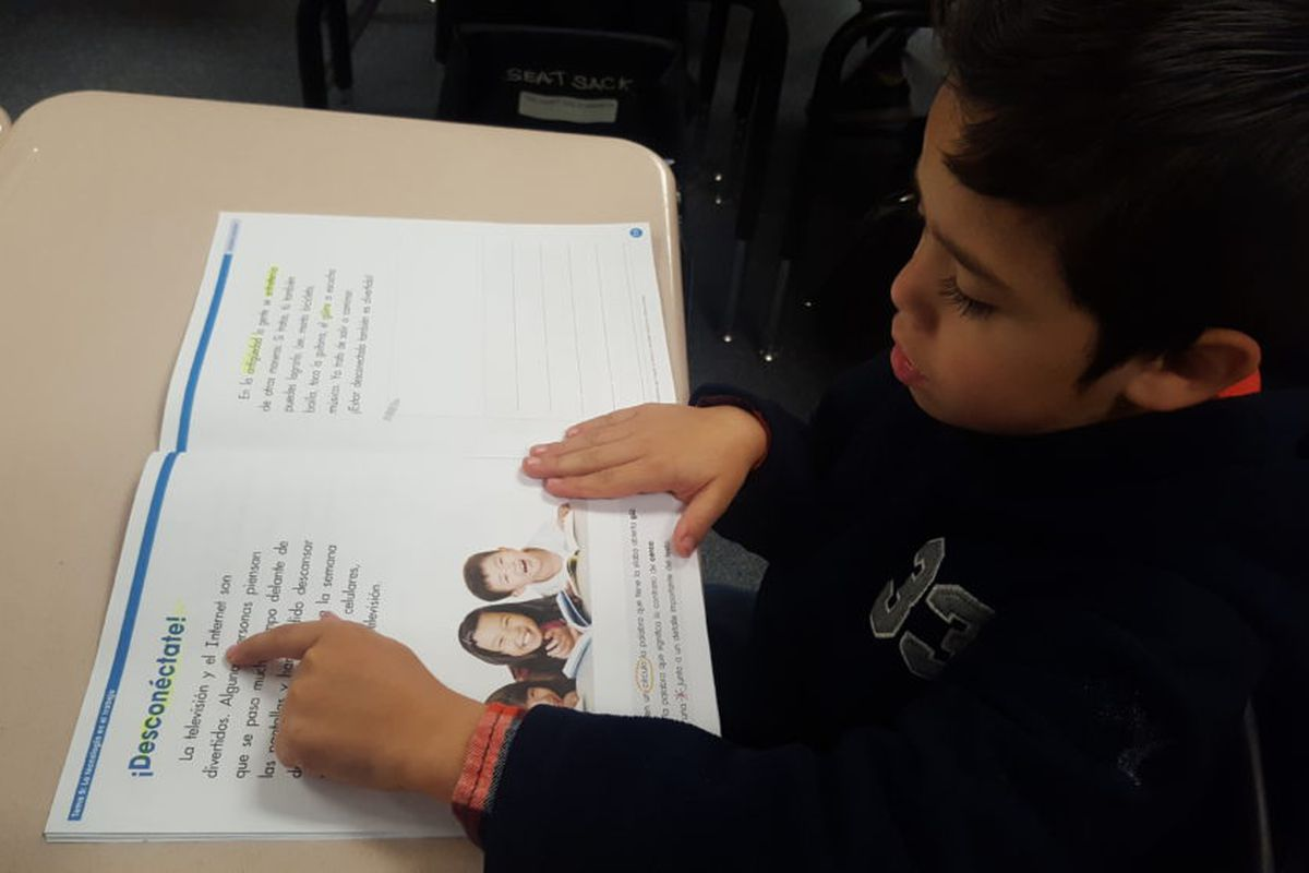 A first-grade student uses his finger to guide himself as he reads in Spanish in a biliteracy classroom in Adams 14.
