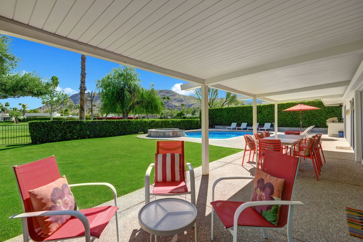 A covered patio features a seating and dining area with red and white furniture.