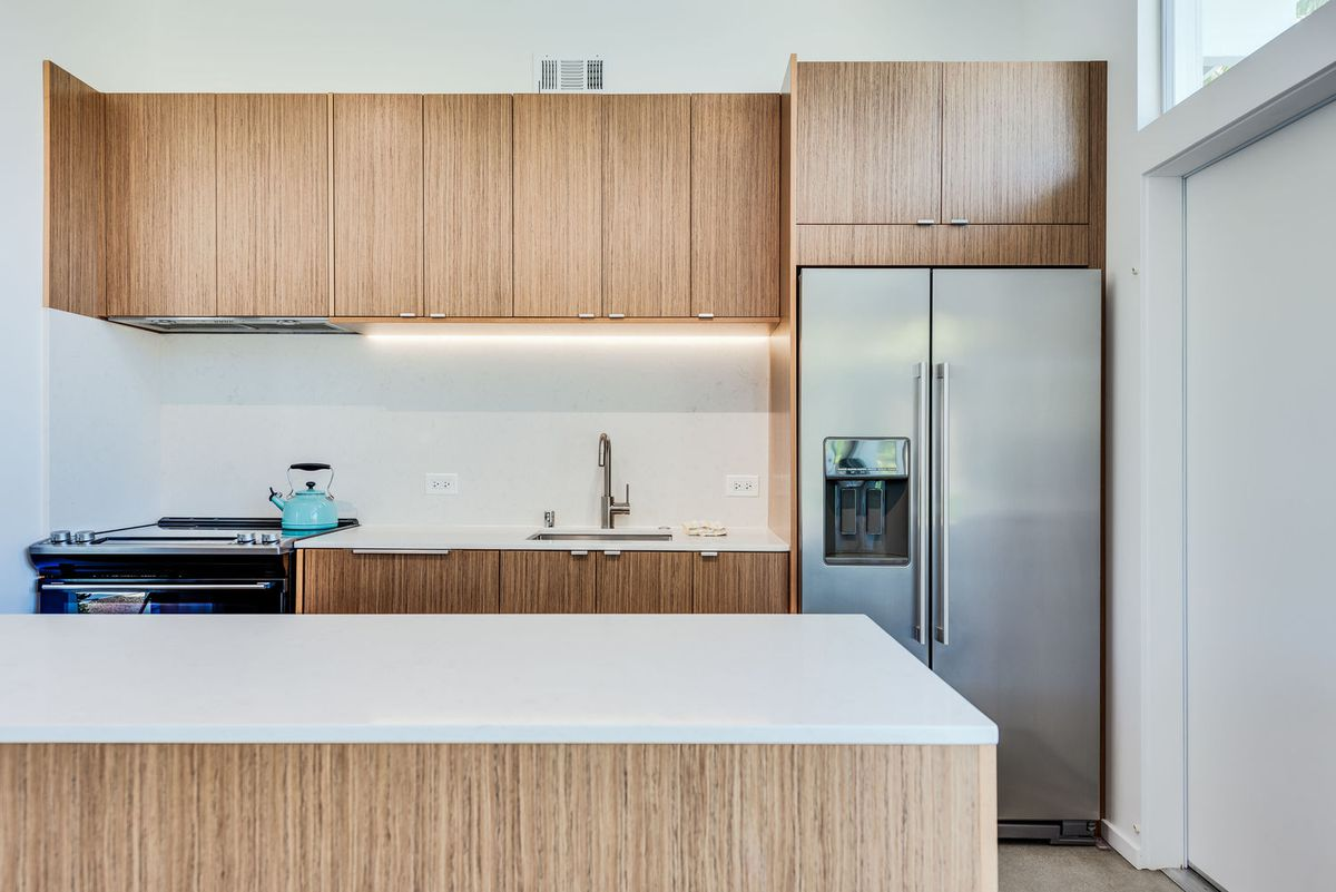 A galley-style kitchen features a silver refrigerator, light birch cabinets, and white countertops.