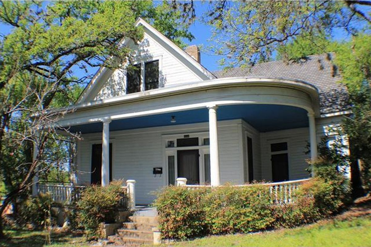 Victorian-ish older home with large, curved front porch, white with blue porch ceiling, gabl