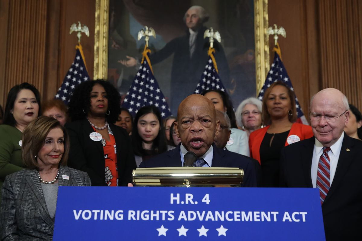"""Lewis speaks surrounded by US flags and Democratic lawmakers at a podium with a sign that reads """"HR 4 Voting Rights Advancement Act."""""""