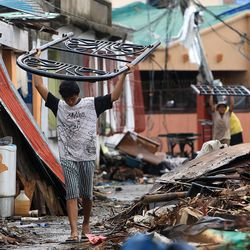A young man carries a bed frame through debris in Tacloban, Friday, Nov. 22, 2013.