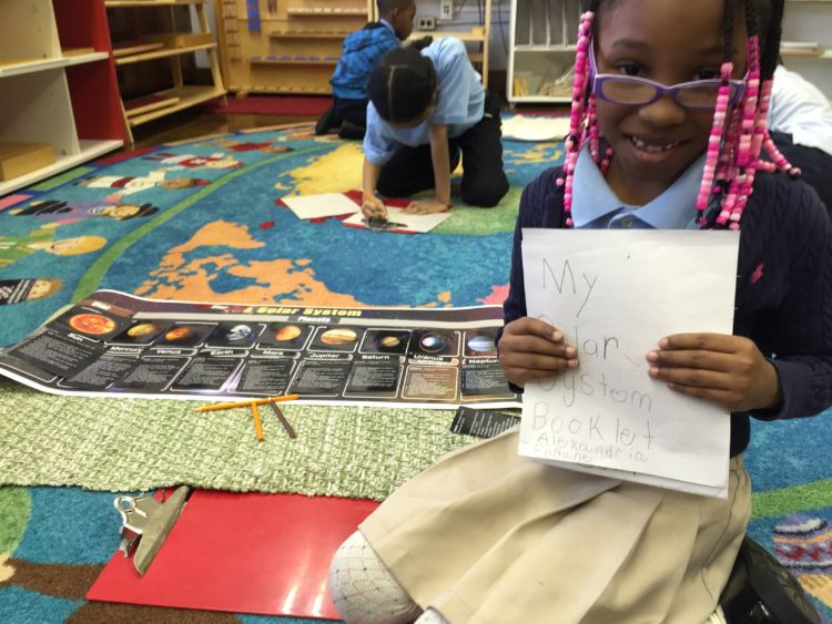 Alexandria Fortune, 7, is making a book about the solar system in her Detroit Montessori classroom.